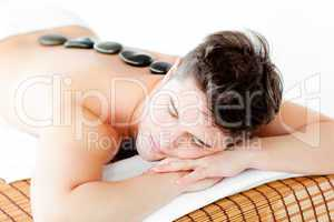 Resting young man lying on a massage table with hot stone on his