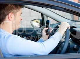Positive young man sending a text while driving