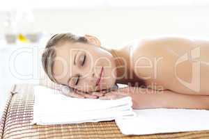 Glad young woman lying on a massage table