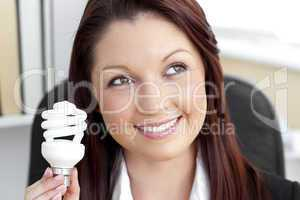 Delighted businesswoman holding a light bulb