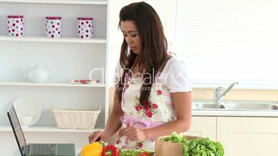 Positive asian woman using her laptop in the morning