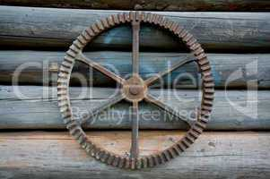 Old farm machine part on log wall