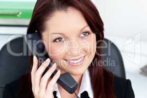 Positive young businesswoman talking on phone