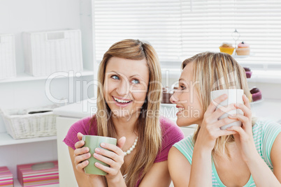 Joyful caucasian friends drinking coffee after baking