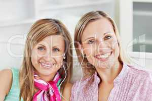 Captivating two female friends listen to music smiling at the ca