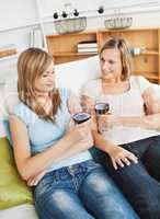 Charming two women drinking wine sitting on a sofa