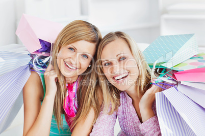 Glowing two women holding shopping bags smiling at the camera