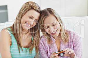Two gorgeous women using a digital camera at home