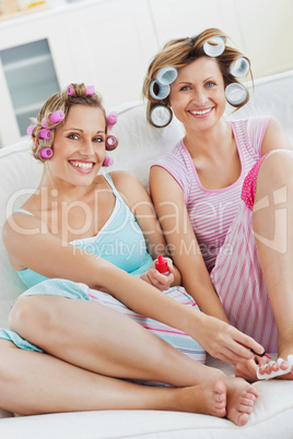 Cheerful female friends doing pedicure and wearing hair rollers