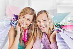 Delighted two women holding shopping bags smiling at the camera