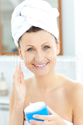 Pretty young woman putting moisturizer on her face looking at th