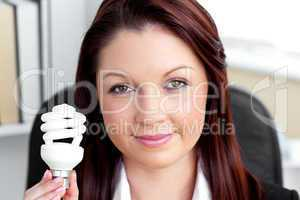 Confident young businesswoman holding a light bulb looking at th