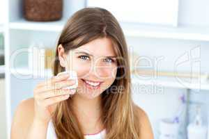 Beautiful woman putting make-up on her face looking at the camer