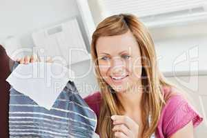Positive young woman sewing clothes at home