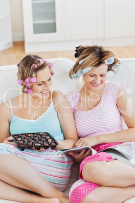 Female friends with hair rollers eating chocolate reading a maga