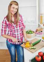 Joyful woman cutting pepper and cucumber at home