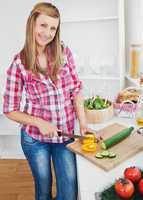 Joyful woman cutting pepper and cucumber at home