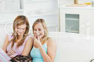 Two beautiful female friends eating chocolate at home