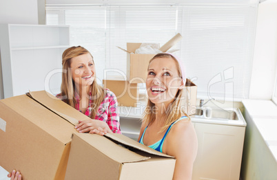 Two radiant women carrying boxes at home