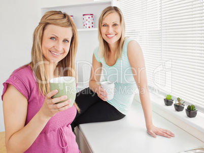 Portrait of two happy women holding cups of coffee at home