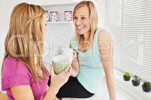 Portrait of two smiling women holding cups of coffee at home