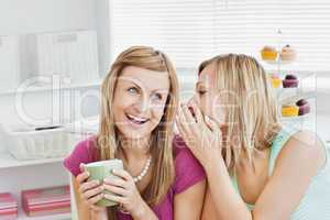 Close female friends talking together with a cup of coffee at ho