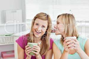 Positive female friends holding a cup of coffee at home