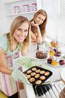 Happy female friends holding cookies in the kitchen