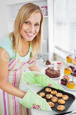 Smiling woman holding cookies in the kitchen