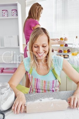 Cheerful woman baking together with her friend at home