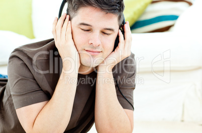 Relaxed man listen to music lying on the floor