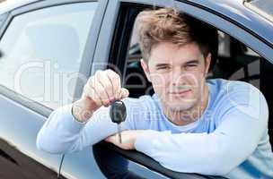 Charming young man holding a car sitting in his car