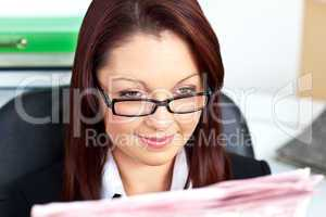 Delighted young businesswoman reading a newspaper