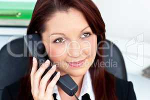 Assertive young businesswoman talking on phone smiling at the ca