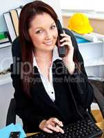 Ambitious businesswoman talking on phone using her computer