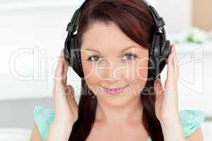Bright woman listening to music with headphones at home
