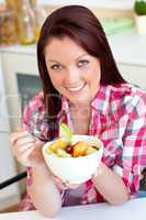 Glowing woman eating a fruit salad for breakfast in the kitchen