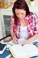 Concentrated student doing her homework at home