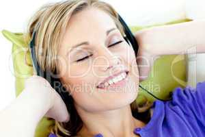 Charming caucasian woman listening to music with headphones lyin