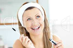 Radiant caucasian woman using mascara in the bathroom