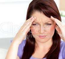 Dejected woman having a headache sitting in the living-room