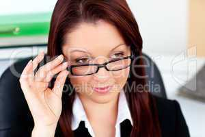 Serious businesswoman holding her glasses
