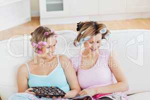 Close female friends with hair rollers eating chocolate reading