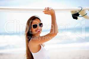 Happy young woman with surfboard on head