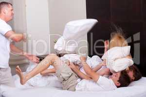 Happy family playing with pillows on the bed