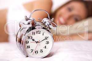 Beautiful smiling woman in white bikini with Alarm clock