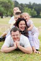 Happy family piled up  on the park and looking at you