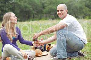 Couple sitting in blanket smiling with picnic mode