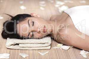 Beautiful lady with white flowers in spa treatment