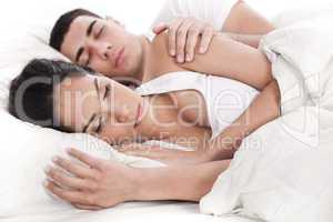Couple lying in bed sleeping together